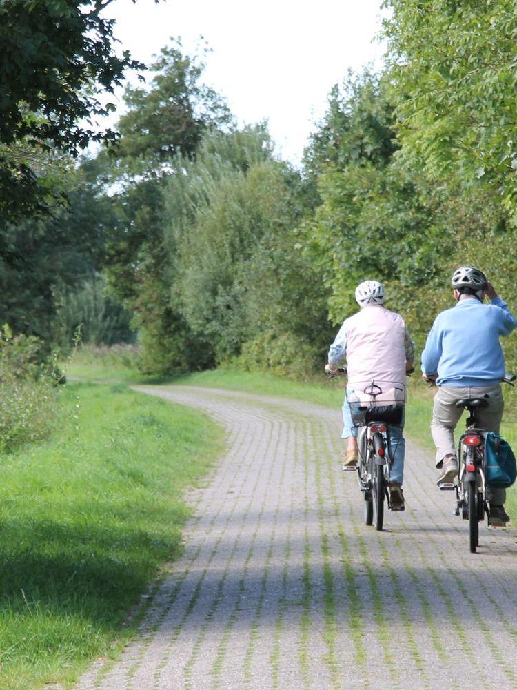 Zwei Radfahrer fahren entlang eines landwirtschaftlichen Weges