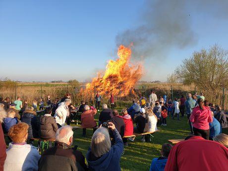 Das Osterfeuer brennt und die Menschen sitzen um das Feuer herum