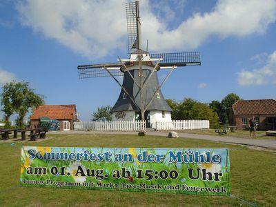 Ein Banner weist vor der Mühle auf das anstehende Sommerfest an der Mühle hin.
