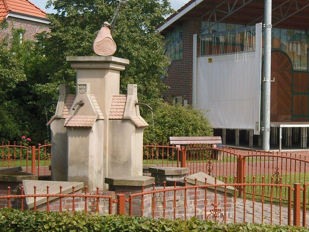 Alter Brunnen mit einem Schinken oben abgebildert. Im Hintergrund die große Bühne.